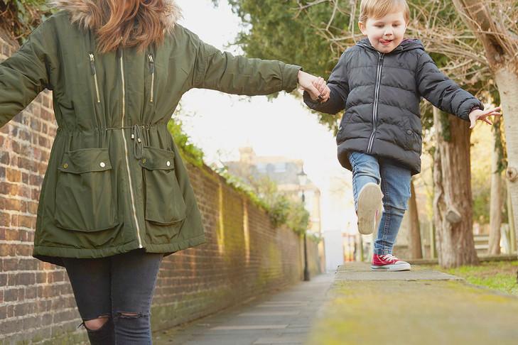 Jeune maman qui tient son fils par la main dans la rue.